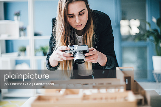 Architect taking photo of architectural model in office - p300m1581712 by Gustafsson