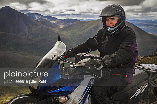 Adventure motorcyclist sitting on his Kawasaki KLR 650 at the top of a hill off of the Denali Highway, Southcentral Alaska, Summer