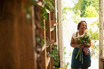 Happy female florist with flower bouquet in shop doorway - p1023m2261931 by Martin Barraud