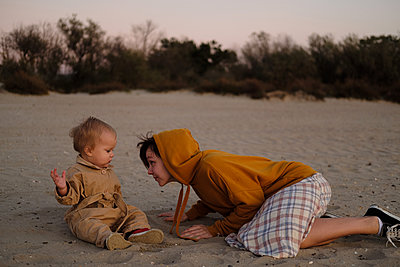 Woman with baby playing on beach - p1363m2142795 by Valery Skurydin