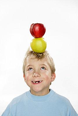 Junge mit Äpfeln auf dem Kopf - p730m668328 von Adrian Bischoff