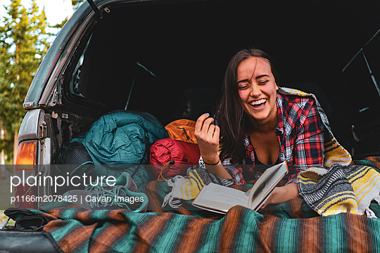 Camp Vibes - Young Woman Laughing while car camping. - p1166m2078425 by Cavan Images
