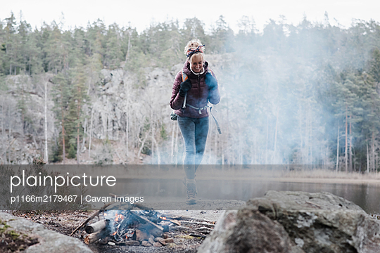 woman walking on a rock towards a campfire by a lake in Sweden - p1166m2179467 by Cavan Images