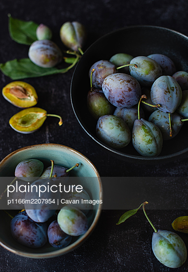 Close up of bowls of fresh plums against a black background. - p1166m2207954 by Cavan Images