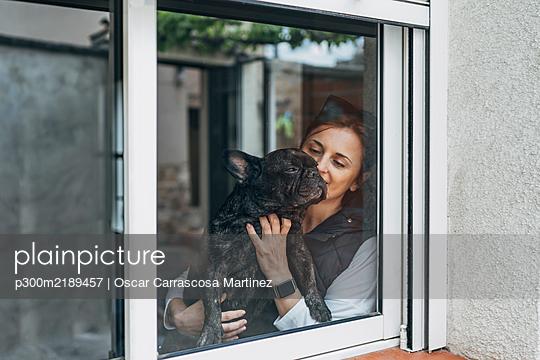 Woman cuddling her bulldog behind window - p300m2189457 by Oscar Carrascosa Martinez