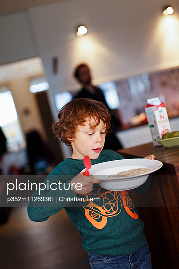 Sweden, Boy (6-7) carrying plate with cereal