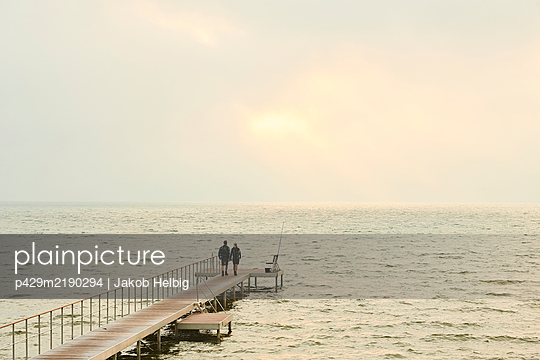 Two people standing on a jetty looking out over water to a pale sunset.  - p429m2190294 by Jakob Helbig