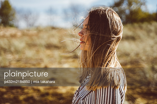 Junge Frau steht entspannt am Strand - p432m2184850 von mia takahara