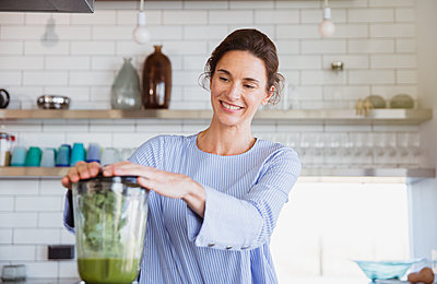 Smiling woman making healthy green smoothie in blender in kitchen - p1023m2187409 by Sam Edwards