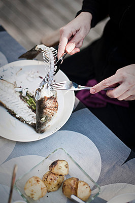 Close-up of woman eating fish with fork and table knife - p4269340f by Ulf Börjesson
