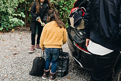 Sisters loading luggage in electric car while going for picnic at weekend - p426m2195240 by Maskot