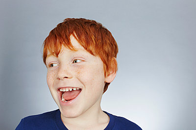 Studio portrait of smiling red haired boy looking sideways - p429m1417771 by Emma Kim