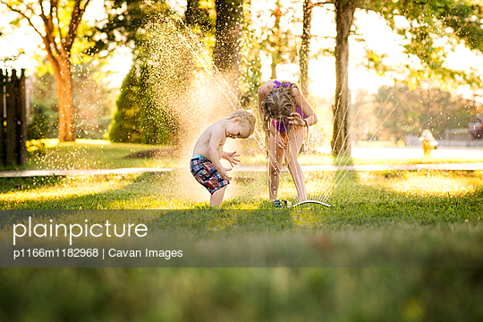 Cheerful siblings playing with water in backyard - p1166m1182968 by Cavan Images