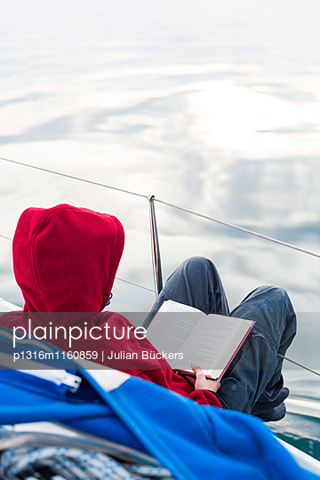 Frau liest an Deck von einem Segelboot, Golf von Triest, Görz, Friaul-Julisch Venetien, Italien - p1316m1160859 von Julian Bückers