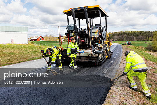Workers putting new road surface - p312m2237200 by Thomas Adolfsén