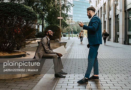 Businessman discussing with male colleague on footpath in city - p426m2239052 by Maskot