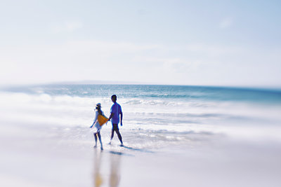 two young people walking along a picturesque beach - p1072m1348935 by Stephen Allsopp