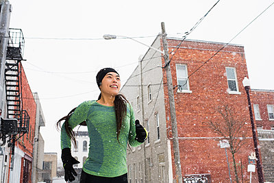 Happy young female runner in knit hat running in snowy street - p429m1407917 by Hugh Whitaker