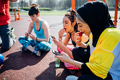 Calisthenics class at outdoor gym, young women sitting looking at smartphones and eating fruit - p429m2098340 by Eugenio Marongiu