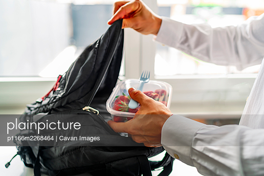 young man storing his healthy food tupperware in his backpack - p1166m2268464 by Cavan Images
