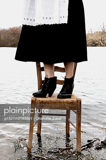 Chambermaid standing on chair by a lake - p1521m2193361 by Charlotte Zobel