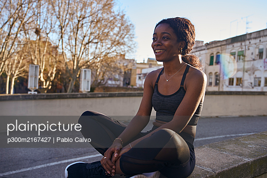 Young smiling sportswoman sitting on a wall - p300m2167427 by Pablo Calvo