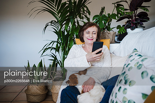Smiling senior woman using mobile phone while sitting with dog on sofa at home - p300m2265648 by Eva Blanco
