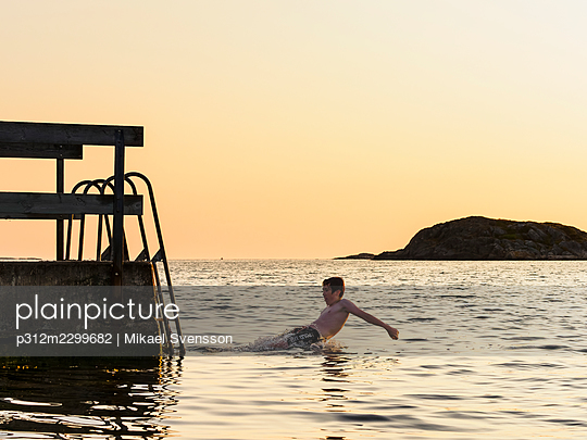 Boy jumping into sea - p312m2299682 by Mikael Svensson