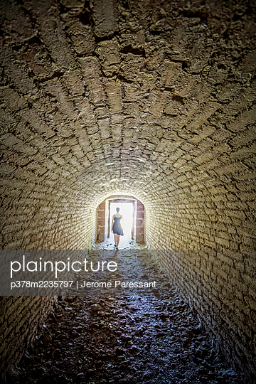 Girl walking through tunnel - p378m2235797 by Jerome Paressant