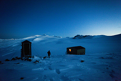 A refuge on the  Wapta Traverse, a 4 day hut-to-hut ski tour. A skier leaves the main hut to use the outhouse restroom. - p1100m876253f by Michael Hanson