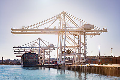Low angle view of cranes at commercial dock against clear sky - p1166m1142550 by Cavan Images