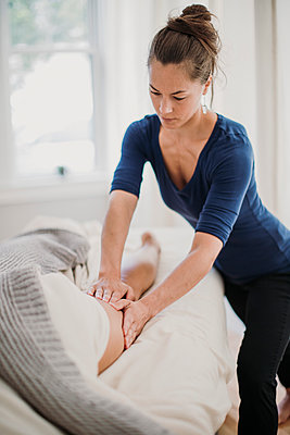 A female massage therapist concentrates on her patient's thigh muscle - p1166m2107027 by Cavan Images