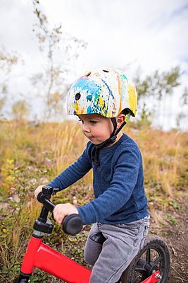 Side view of young boy riding red bike. - p1166m2153345 by Cavan Images