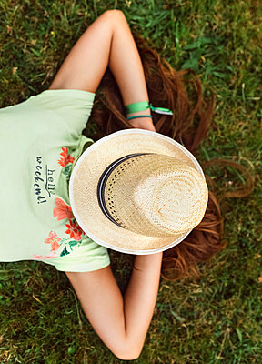 Girl with straw hat on her face lying on a meadow - p300m1192219 by Marco Govel