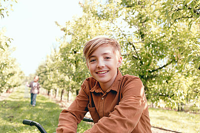 Blond boy smiling while sitting in orchard - p300m2275636 by Katharina Mikhrin