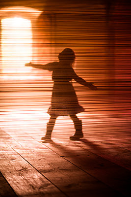 Silhouette of girl dancing on wooden floor - p312m1228850 by Peter Rutherhagen