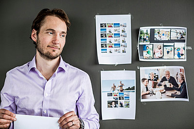Mid adult businessman holding paper while standing against wall in office - p426m811562f by Maskot