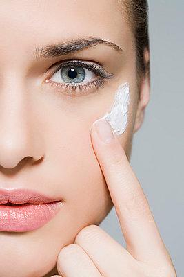 Woman applying moisturiser - p9248608f by Image Source
