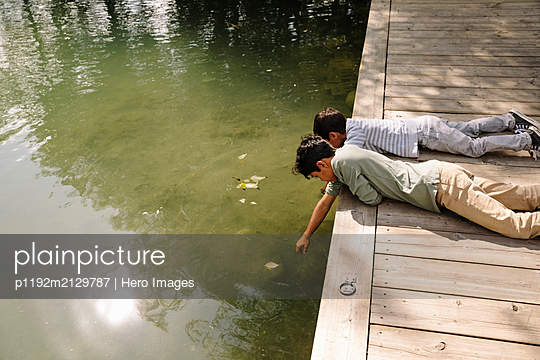 Two boys leaning over jetty and touching water - p1192m2129787 by Hero Images