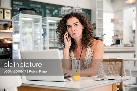 Mature woman sitting in coffee shop, using laptop, talking on he phone - p300m2069947 by Robijn Page