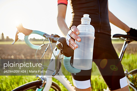 Female cyclist holding water bottle, mid section - p429m2091424 by Maria Fuchs