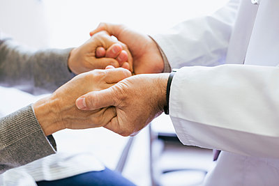 Close-up of doctor holding senior patient hands - p1166m1473708 by Cavan Images