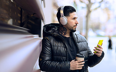 Hipster man with headphones holding coffee cup and smart phone while looking away - p300m2252636 by Jose Carlos Ichiro
