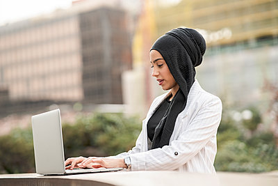 Beautiful Arab businesswoman wearing headscarf using laptop outdoors - p300m2265658 by Jose Carlos Ichiro