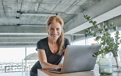 Smiling mature woman using laptop at table in loft apartment at home - p300m2266111 by Jo Kirchherr