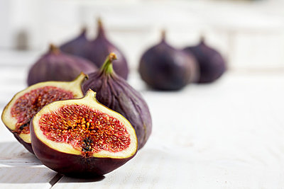 Sliced and whole figs on white wooden table, studio shot - p300m873868f by Dieter Heinemann