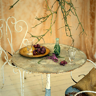 Still life of rustic vintage metal table and chairs with tableware - p349m695184 by Emma Lee