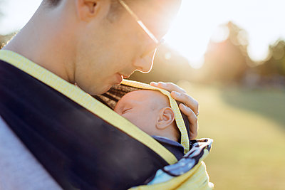 Father carrying baby boy in baby carrier - p429m1569552 by Katie Rollings