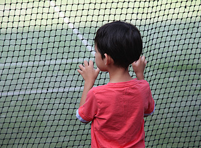Little Boy looking through a net - p664m1160173 by Yom Lam