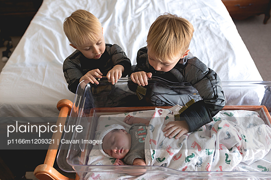 High angle view of brothers looking at baby girl sleeping in crib - p1166m1209321 by Cavan Images